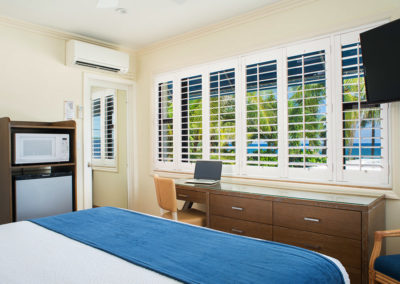 Photo of one of our rooms displaying the foot of a bed and windows showing sunny day outside.